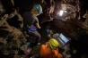 古生物学者のアシュリー・クルーガーとともに横穴を調査するエリオット(左)。洞窟探検のスキルがあり、狭い洞窟の奥まで入れる細身の女性研究者6人が発掘作業を行った。地上で様子を見守るバーガーが、パソコンの画面に映っている。