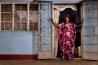 <b>ウガンダ</b><br>1週間前に夫を亡くした54歳のソロメ・セチムリ。葬儀の日に武器を手にした夫の親族に脅迫され、資産を奪われそうになった。ルウェロ県にある自宅の戸口に立ち、この家を守り抜く覚悟を示す。