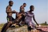 シエラレオネ北西部の村で雑貨を売る娘が、3人の少年の近くに腰かけて一休みする。この川辺では、少女たちが洗濯をし、少年たちは魚を釣る。少女に対する犯罪がめったに罰せられない同国では、学校に通わず、家計を助けるために街角で働く少女たちが被害に遭う危険性が非常に高い。